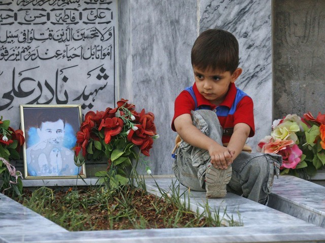 Five-year old Sahil Hazara sits on the grave of his brother Nadir Ali, who was killed by unidentified gunmen, at the Hazara graveyard in Mehrabad, Quetta. PHOTO: REUTERS