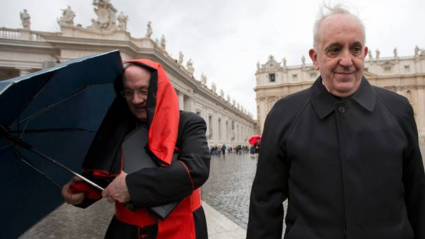 Canadian Marc Cardinal Ouellet, left, holds on to his umbrella next to Argentine Cardinal Jorge Mario  Bergoglio as they walk in St. Peter's Square after attending a cardinals' meeting, at the Vatican, Wednesday, March 6, 2013.