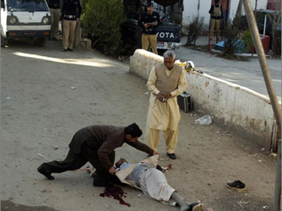 Dead body of a Shia mourner killed by Deobandi terrorists. See the indifferent postures of the policemen.