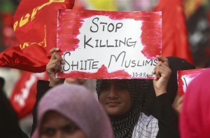 A woman holds a sign amidst hundreds of Pakistani followers of Shia Islam protesting against targeted killings of Shia Muslims in Karachi