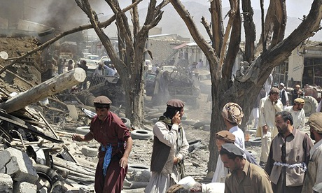 Afghan villagers gather at the site of the car bomb attack in Urgun