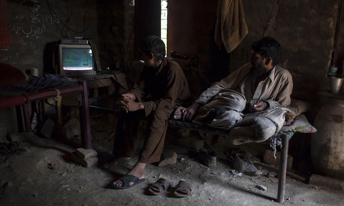 Miners watch TV in a room at a coal field in Choa Saidan Shah