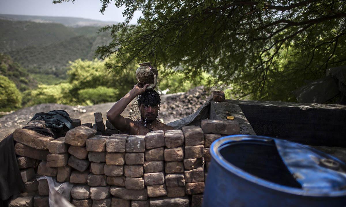A miner washes after finishing his shift at a coal mine in Choa Saidan Shah, Punjab province