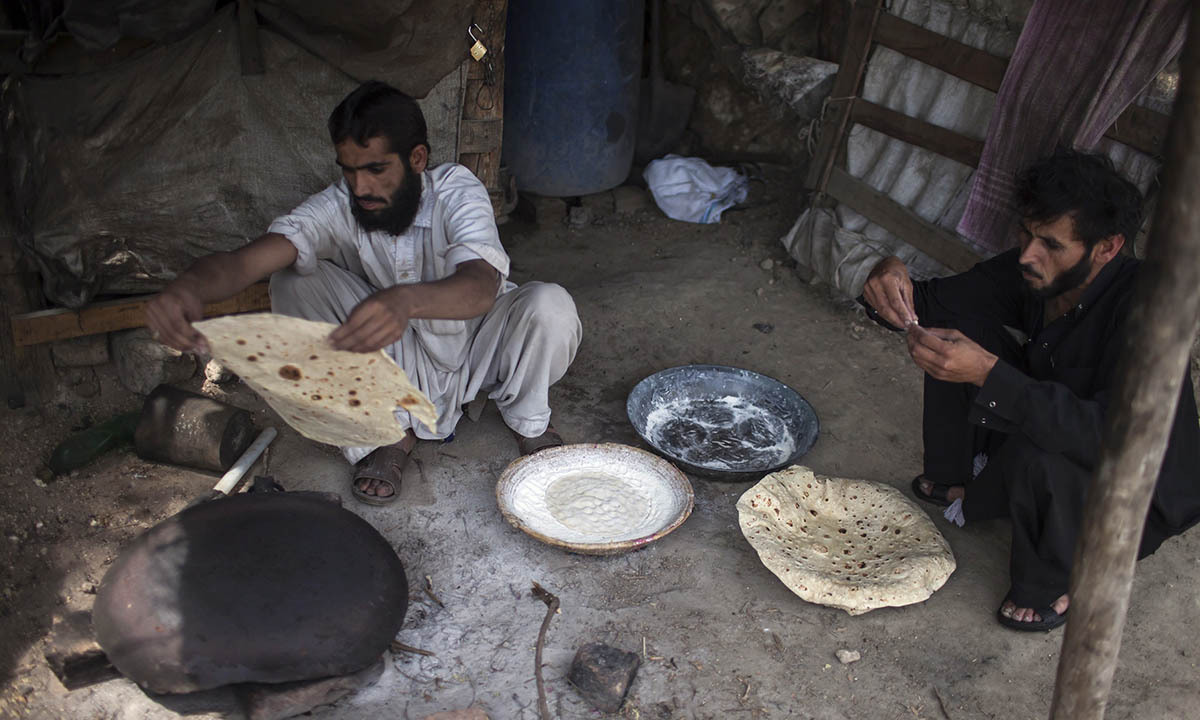 A miner cooks Pashtun roti after finishing his shift at a coal mine in Choa Saidan Shah, Punjab province