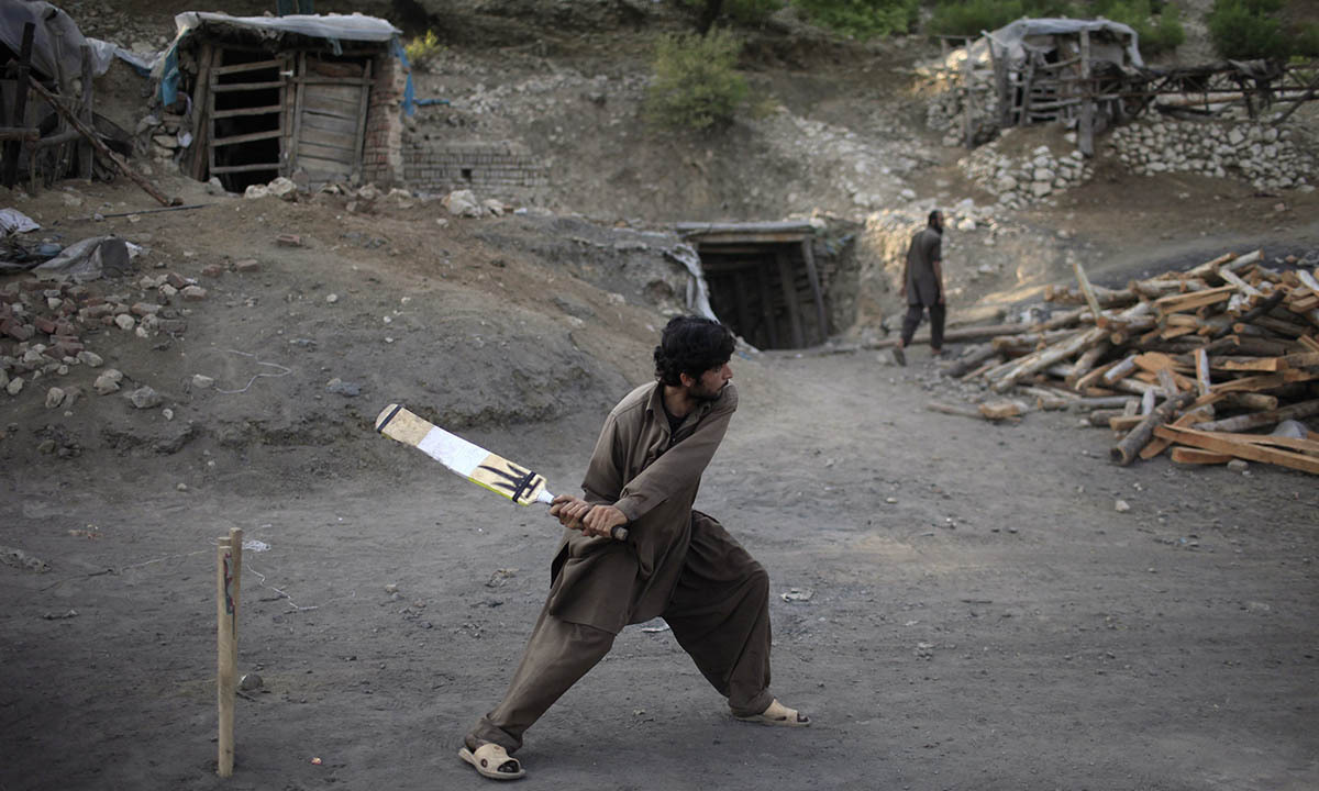 A miner plays cricket in the evening at a coal field in Choa Saidan Shah, Punjab province