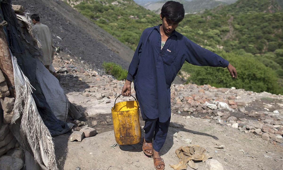 Samiullah carries water for his uncle's bath at a coal field in Choa Saidan Shah, Punjab province