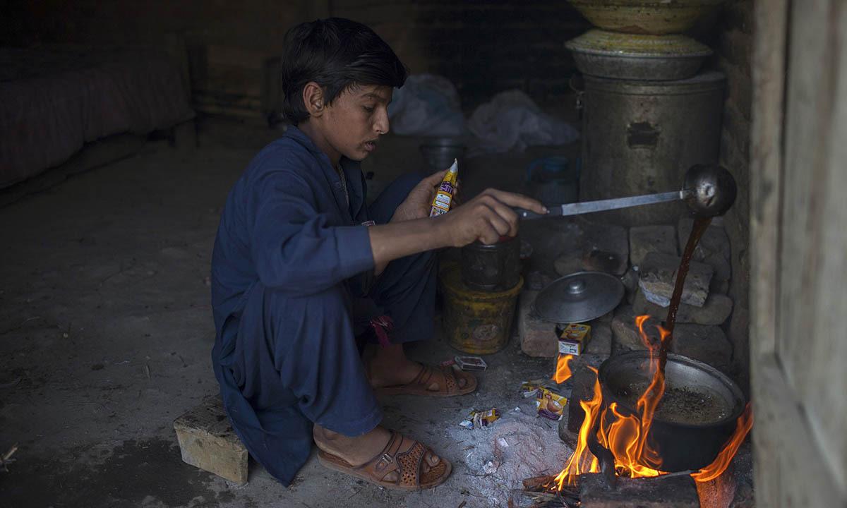 Samiullah prepares tea after finishing work at a coal mine in Choa Saidan Shah, Punjab province