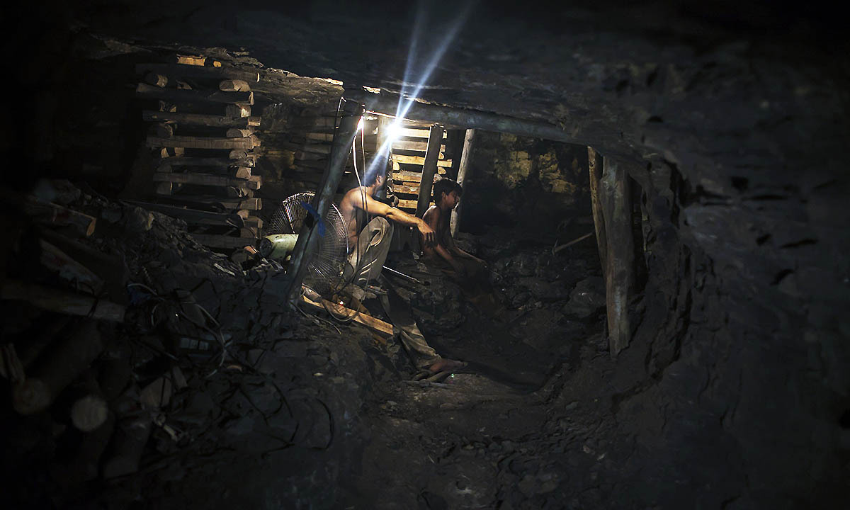 Samiullah sits at the coal face to observe the process of coal mining, underground in Choa Saidan Shah, Punjab province