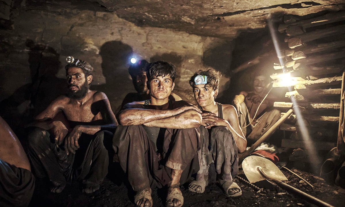 Miners pose for a photograph at the coal face inside a mine in Choa Saidan Shah, Punjab province