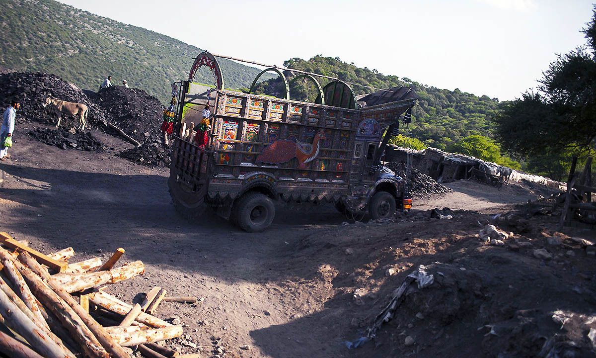 A truck drives past a coal field in Choa Saidan Shah, Punjab province