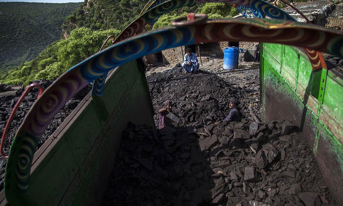 A miner loads coal onto a truck outside a mine in Choa Saidan Shah, Punjab province