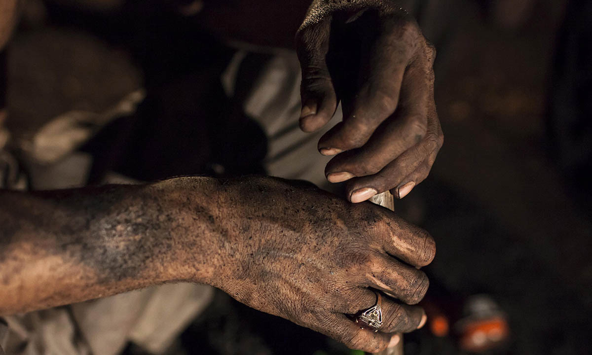 A miner covered in coal dust sits inside a mine in Choa Saidan Shah, Punjab province