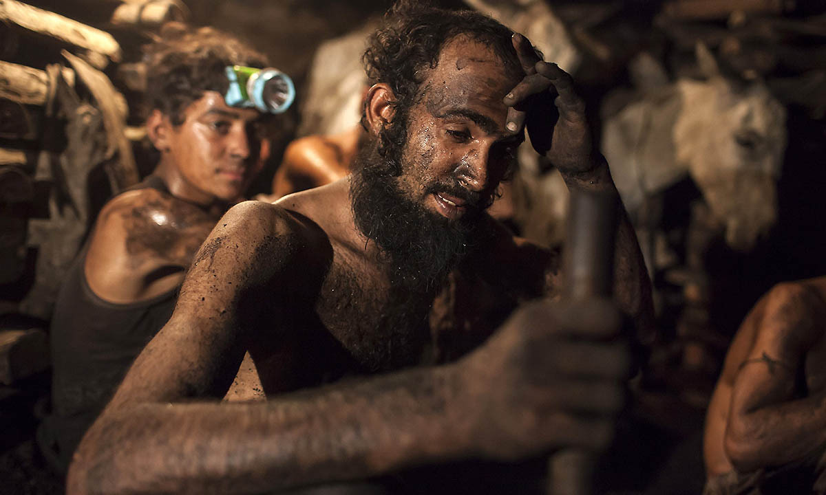 A miner wipes sweat from his forehead inside a coal mine in Choa Saidan Shah, Punjab province