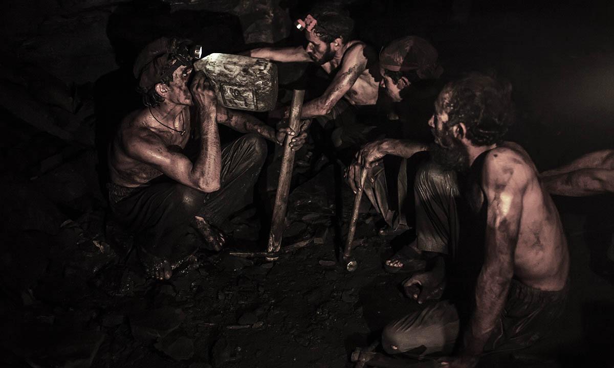 Miners take a break to drink water inside a coal mine in Choa Saidan Shah, Punjab province