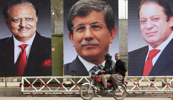 Men ride a motorcycle past giant portraits of  Pakistan's President, Prime Minister and the Turkish Prime Minister displayed along a road in Islamabad