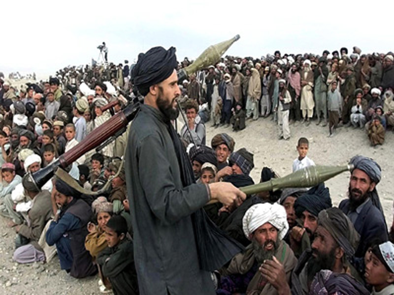 A Taliban soldier armed with RPG launchers controls unruly and angry refugees on the arrival of UN High Commissioner for Refugees Ruud Lubbers, 30 April 2001, at the Maslakh refugee camp near Herat, Afghanistan. More than 110,000 people who fled from drought and fighting have taken refuge at the overcrowded camp living in miserable conditions.  Lubbers, visiting the Iran-Afghan border, called 30 April for a ceasefire in Afghanistan where war and drought have left a million people facing famine.   AFP PHOTO/POOL