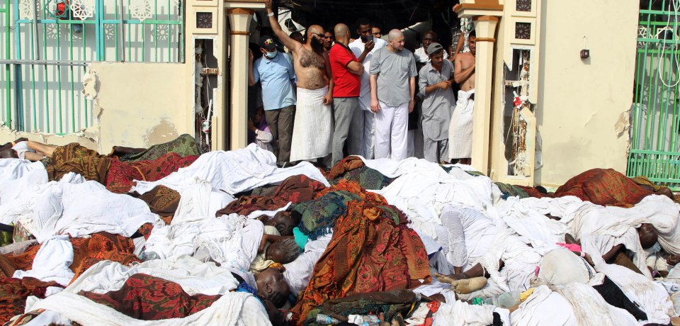GRAPHIC CONTENT Saudi emergency personnel stand near bodies of Hajj pilgrims at the site where at least 717 were killed and hundreds wounded in a stampede in Mina, near the holy city of Mecca, at the annual hajj in Saudi Arabia on September 24, 2015. The stampede, the second deadly accident to strike the pilgrims this year, broke out during the symbolic stoning of the devil ritual, the Saudi civil defence service said. AFP PHOTO / STR (Photo credit should read STR/AFP/Getty Images)