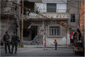 Syrian soldiers and children at a checkpoint in the besieged and devastated city of Homs, Syria, March 23, 2014. For both sides of Syria's civil war, Homs, a central Syrian crossroads with a diverse prewar population of 1 million, is crucial to the future. (Sergey Ponomarev / The New York Times)