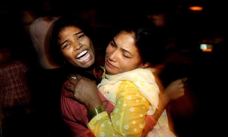 Family members consoling each other after their relative was killed in today's blasts. Image courtesy of DAWN /AP