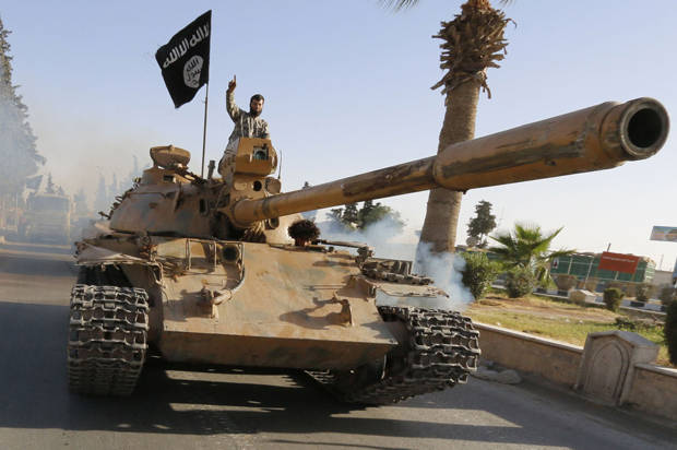 "Militant Islamist fighters on a tank take part in a military parade along the streets of northern Raqqa province June 30, 2014. Militant Islamist fighters held a parade in Syria's northern Raqqa province to celebrate their declaration of an Islamic ""caliphate"" after the group captured territory in neighbouring Iraq, a monitoring service said. The Islamic State, an al Qaeda offshoot previously known as Islamic State in Iraq and the Levant (ISIL), posted pictures online on Sunday of people waving black flags from cars and holding guns in the air, the SITE monitoring service said. REUTERS/Stringer (SYRIA - Tags: POLITICS CIVIL UNREST CONFLICT) - RTR3WJA0"